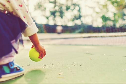 child pick up tennis ball